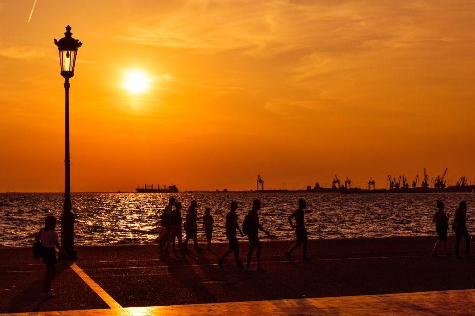 Silhouettes of people walking alongside the waterfront of Thessaloniki, Greece