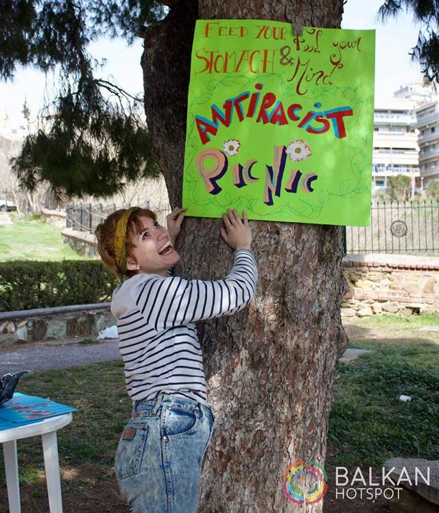"Smiling girl with a sign that reads ""Feed your stomach and feed your mind - Antiracist picnic."""